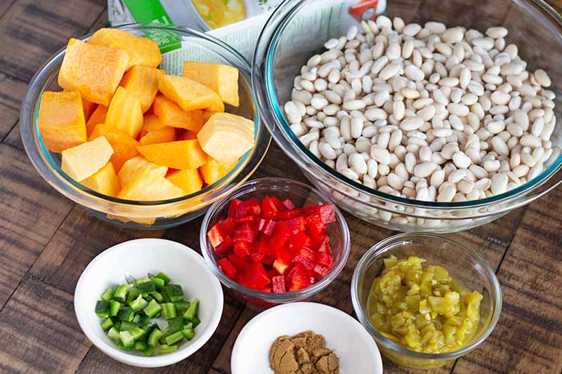 Oblique overhead image of a large glass bowl of soaked great northern beans, a medium-sized bowl of cubed butternut squash, and small glass and ceramic bowls of diced red bell pepper, diced canned green chilis, diced jalapeno, and groudn cumin, with a box of vegetable broth on a wood surface.