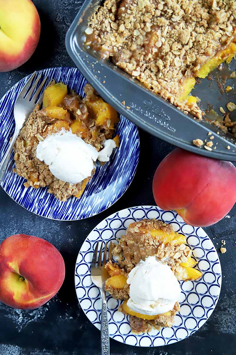 Vertical overhead image of two blue and white plates and a metal baking pan of peach crumble with a brown sugar topping, with each portion topped with a scoop of vanilla ice cream and a fork on the edge of each plate, on a gray surface with three whole orange and yellow stone fruits.