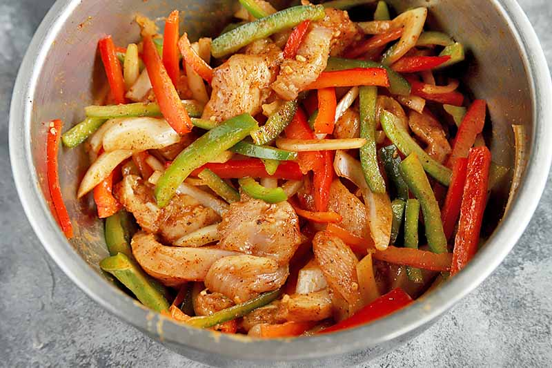 Horizontal image of a metal bowl with a spiced uncooked mix of peppers and chicken strips.