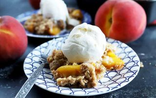 Horizontal nearly head-on image of a blue and white patterned plate of homemade peach crisp topped with a scoop of vanilla ice cream with a fork to the left, with an identical plate in the background and two whole stone fruits, on a gray surface.