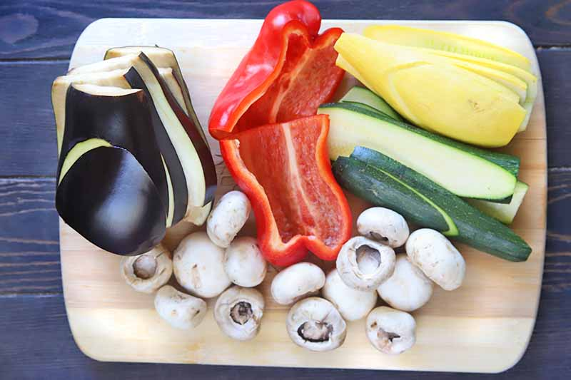 Horizontal image of eggplant, peppers, mushrooms, and squash prepped and sliced on a wooden cutting board.