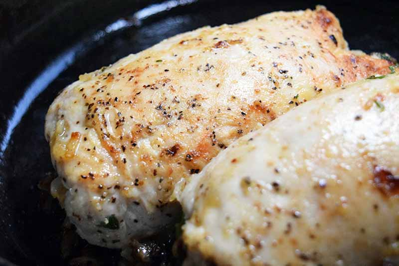 Stuffed chicken breasts sprinkled with salt and pepper, browning in oil in a cast iron pan.