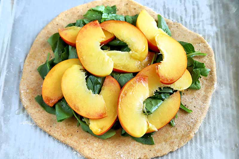 Horizontal oblique overhead image of a rolled out round of pizza dough topped with baby spinach leaves and peach slices, on a piece of waxed paper.