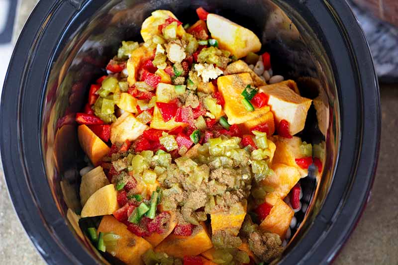 Horizontal overhead image of all of the ingredients required to make a vegetarian chili, in a slow cooker on a kitchen countertop.