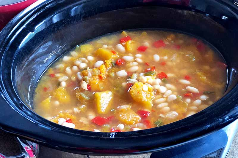 Horizontal oblique overhead image of vegetarian chili in a slow cooker.