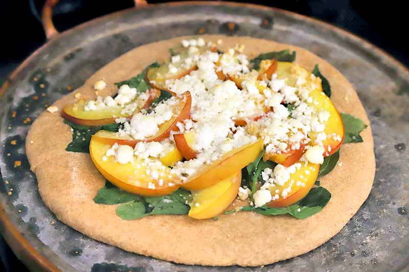 Freshly baked pizza with kefir-spelt crust, peach slices, spinach, and crumbled goat cheese, on a metal pizza pan.