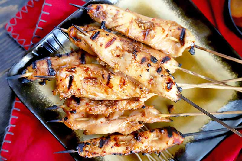 Overhead horizontal image of skewers of grilled chicken piled on a square black and gold serving dish, on top of a red cloth with blue stitching at the border, on a gray wood surface.