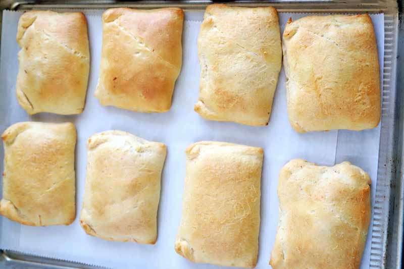 Horizontal overhead image of eight just-baked rectangular stuffed savory pastries, arranged in two rows on a parchment-lined baking sheet.