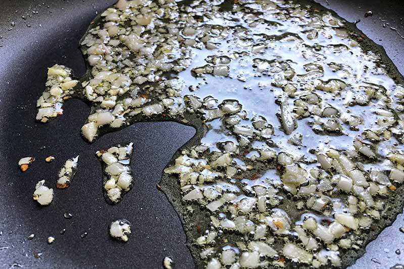 Closeup horizontal image of minced garlic and shallots sauteeing in oil in a nonstick frying pan.