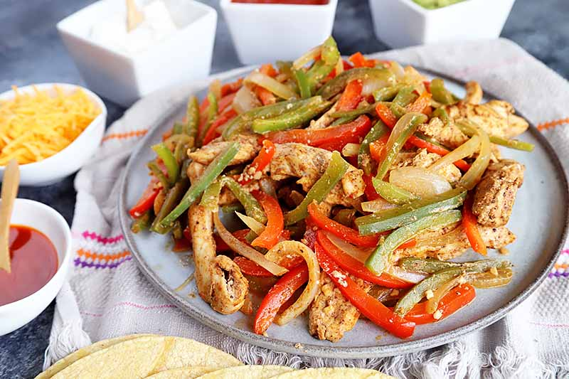Horizontal image of a plate with a spiced chicken and pepper mix.