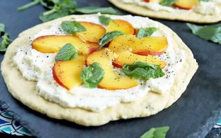 Horizontal image of a round flatbread topped with a thin layer of ricotta cheese, thinly sliced peaches, and basil leaves, on a gray slate surface with another identical appetizer in the background and scattered herbs.