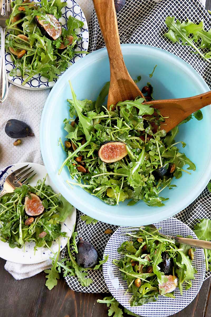 Vertical overhead image of a light blue glass bowl of arugula, fig, and pistachio salad with wooden serving utensils, surrounded by three blue and white patterned plates of salad with forks, on a dark brown wood surface partially covered by a white and a black and white cloth, with scattered fruits, nuts, and leaves.