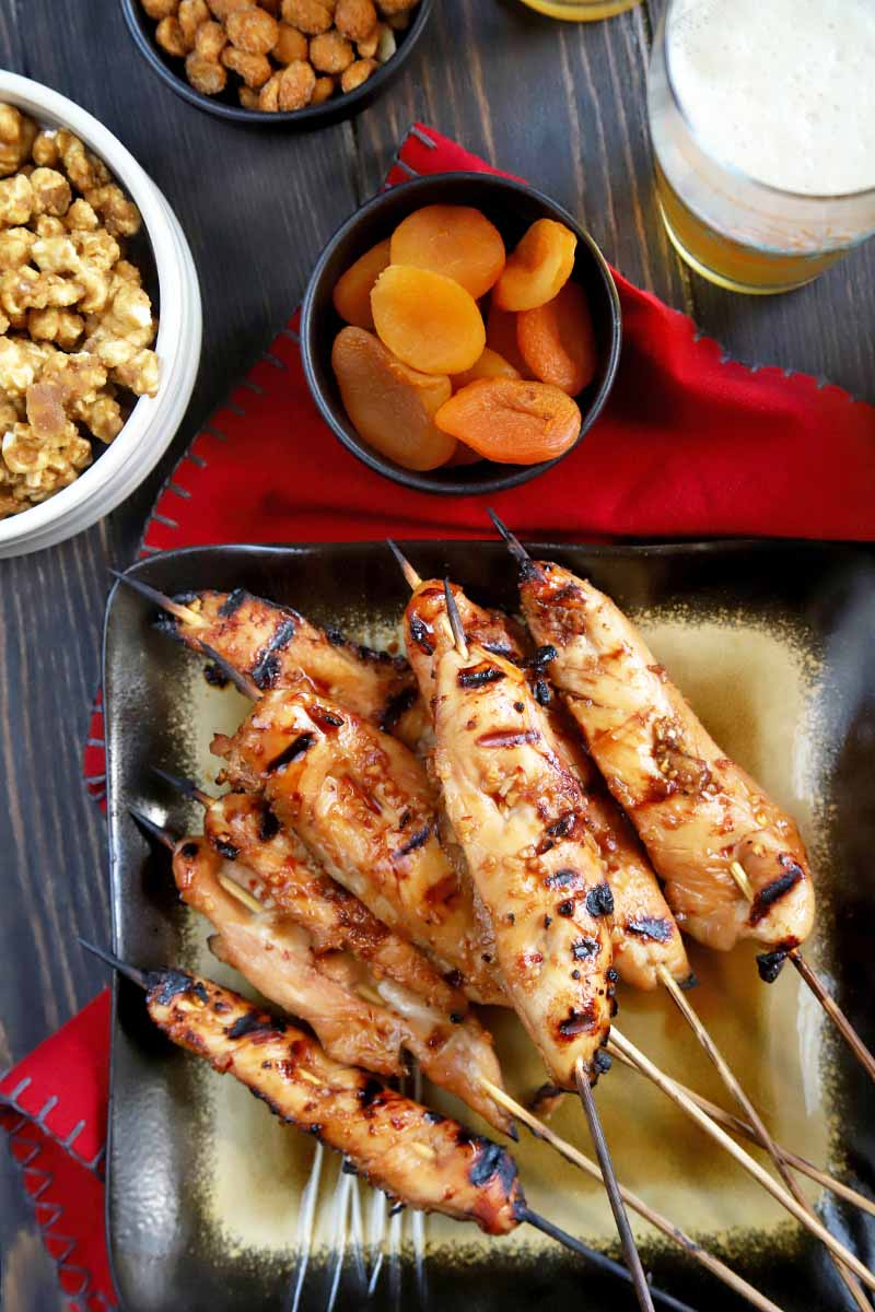 Vertical overhead image of a square gold and black serving platter of grilled chicken on skewers, on a red cloth, with small black dishes of dried fruit and nuts and a larger white bowl of caramel popcorn, with a tall glass of foamy beer on a brownish gray wood surface.