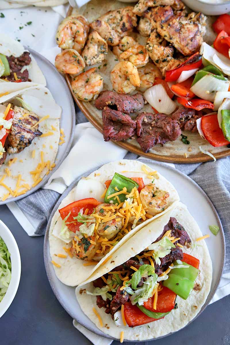 Vertical overhead image of plated fajitas in flour tortillas and topped with shredded cheese, with a serving platter of grilled vegetables, steak, chicken, and shrimp, on a gray surface topped partially with a white cloth.