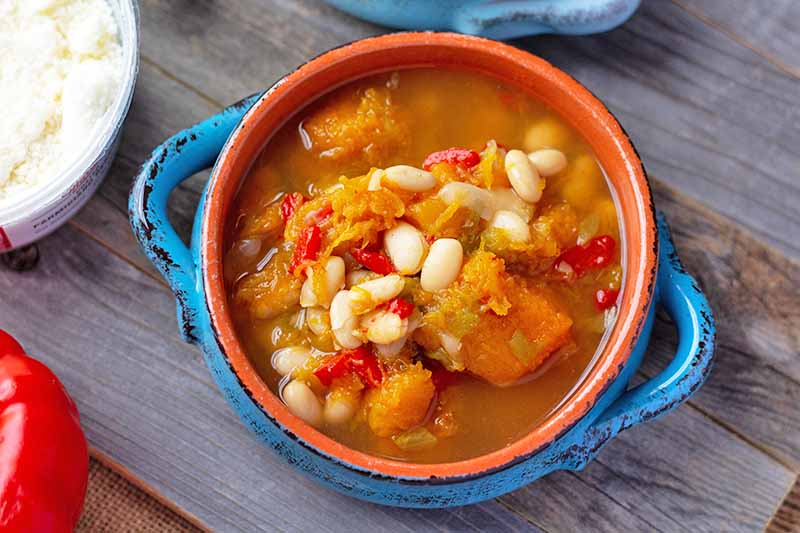 Horizontal overhead image of vegetarian chili with orange broth and squash, in a terra cotta and blue ceramic glazed bowl with two handles, on a wood surface with a red bell pepper, and a plastic container of grated cheese.