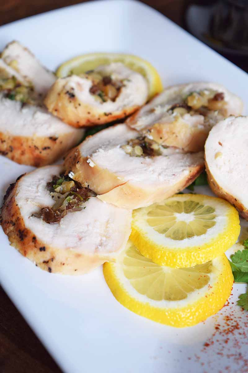 Vertical image of slices of chicken breast stuffed with pine nuts, raisins, and fresh herbs, on a white rectangular ceramic platter with thinly sliced lemon, a sprig of parsley, and a sprinkle of paprika.