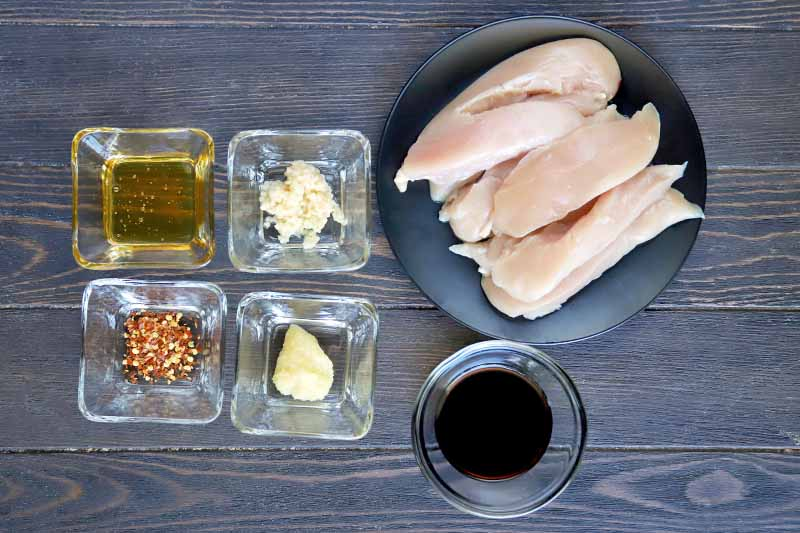 Horizontal overhead image of four small square glass dishes of oil, chili pepper flakes, minced garlic, and grated fresh ginger, with a black plate of raw chicken tenderloins, and a small round glass dish of soy sauce, on a grayish brown wood surface.
