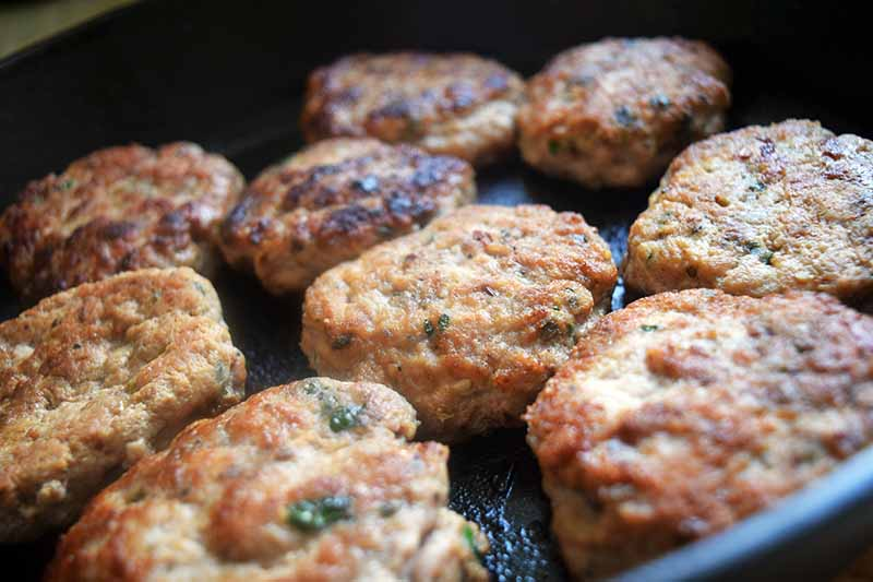 Horizontal image of nine round turkey sausage patties frying in a cast iron pan.