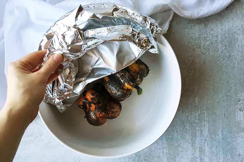 Horizontal image of aluminum foil covering a white bowl with roasted peppers.