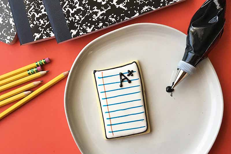 "Horizontal image of a cookie resembling notebook paper, with an ""A+"" piped on top."