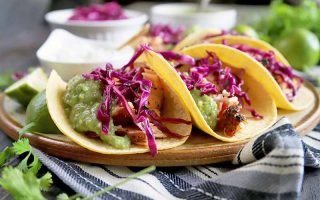 Horizontal image of several salmon tacos in corn tortillas on a tan and brown ceramic serving platter, topped with homemade tomatillo guacamole and red cabbage slaw, on a striped blue, gray, and white cloth with scattered sprigs of cilantro, with small dishes of slaw, sauce, and sour cream in the background, on a brown wood surface.