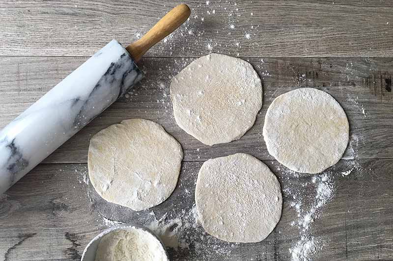 Horizontal image of four flattened mounds of dough next to a rolling pin.