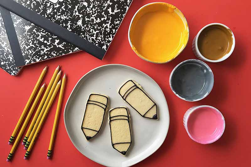 Horizontal image of outlined pencil cookies next to bowls of icing.