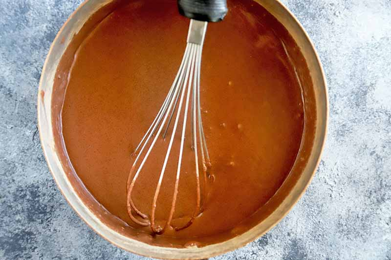 Horizontal image of a whisk in a pot with a light brown liquid mixture.