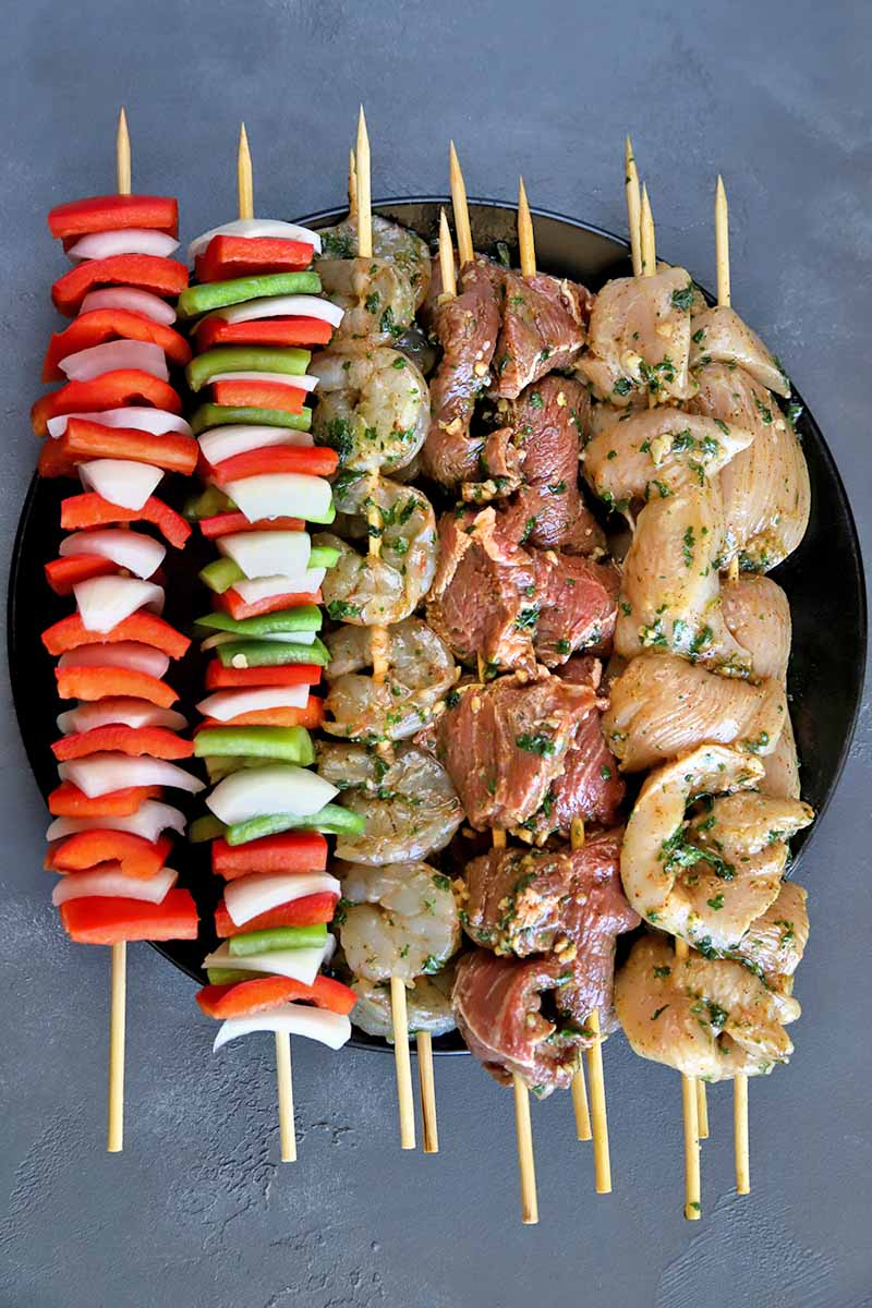 Vertical overhead image of chopped red and green bell pepper, onion, chicken breast, steak, and whole medium-sized shrimp threaded onto wooden skewers, arranged on a black ceramic plate on top of a gray surface.
