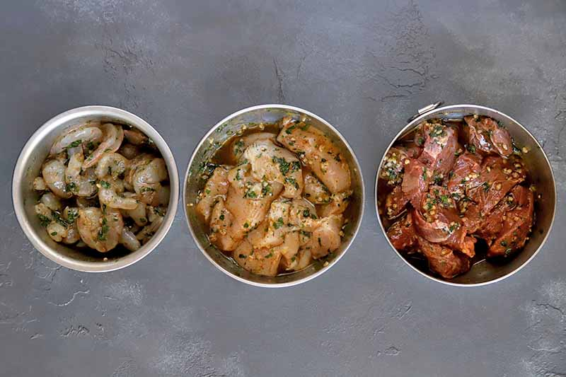 Horizontal overhead image of three small stainless steel bowls of raw shrimp, chopped chicken breast, and chopped steak in a marinade with minced garlic and fresh herbs, on a gray surface.
