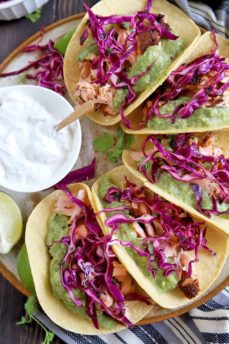 Vertical overhead image of five salmon tacos in yellow corn tortillas on a beige serving platter, topped with tomatillo guacamole and red cabbage slaw, with lime wedges and a small white dish of sour cream, on a brown wood surface with a striped blue, white, and gray cloth.