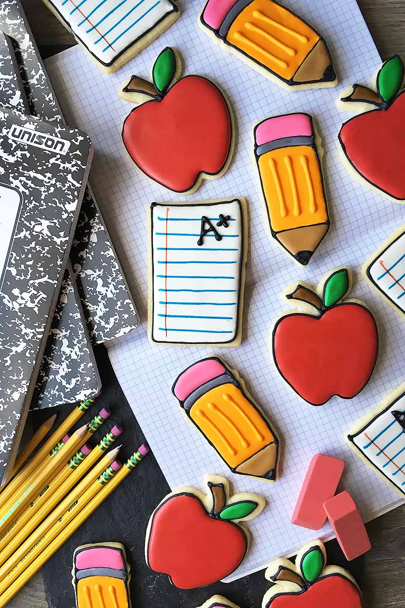 Vertical top-down image of assorted school-themed cookies surrounded by notebooks and pencils.