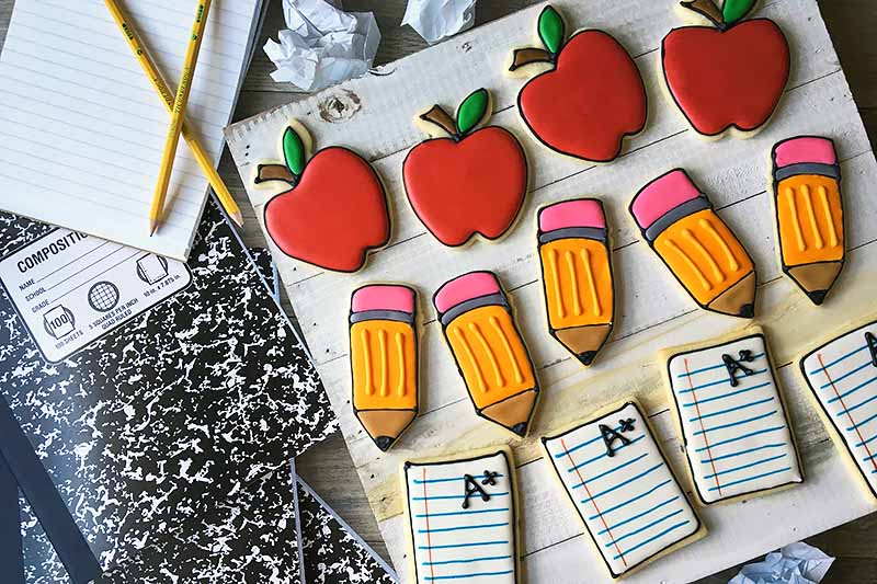 Horizontal image of three rows of cookies with a school theme