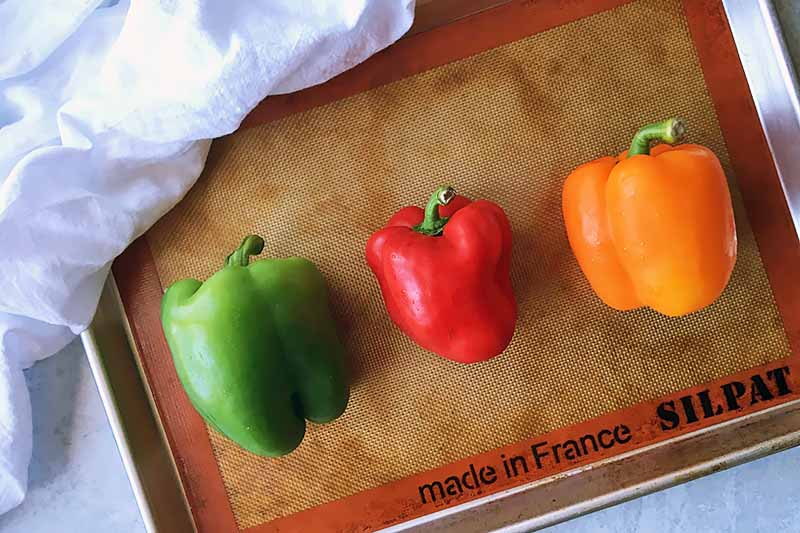 Horizontal image of fresh assorted color vegetables on a baking sheet lined with a silicone baking mat.