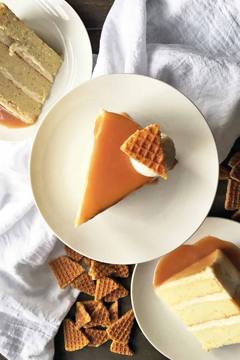Vertical top-down image of an upright slice of caramel cake, surrounded by a white napkin, cookies, and other slices of the same dessert.