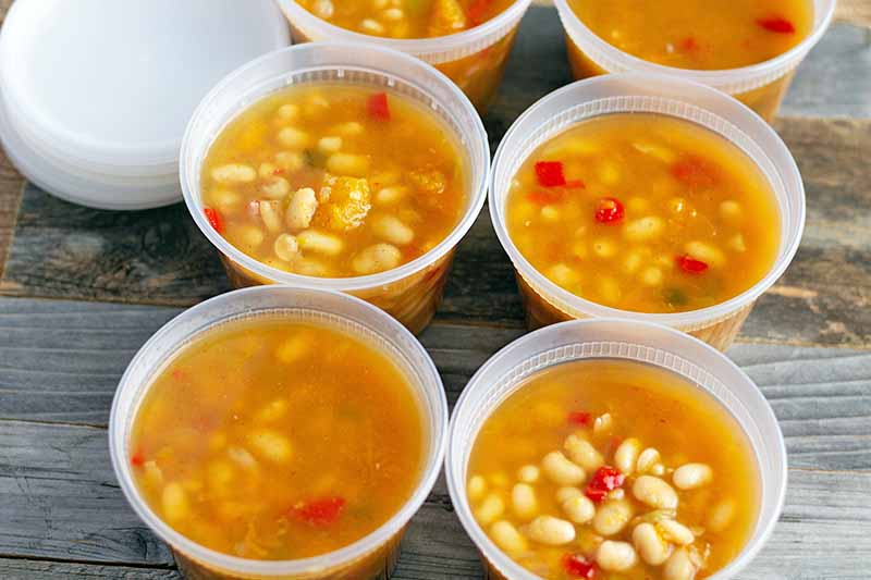 Horizontal oblique overhead image of six pint-sized plastic containers filled with homemade vegetarian chili, with a stack of lids to the left, on an unstained and unvarnished wood surface.