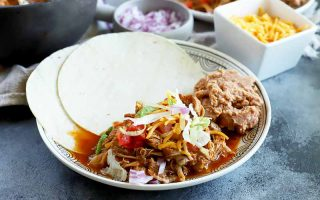 Horizontal image of a plate with two tortilla wraps and shredded meat with assorted toppings.