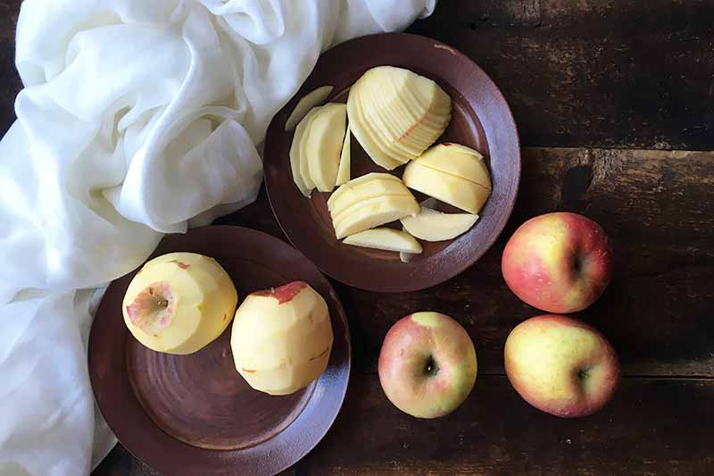 Horizontal image of whole, peeled, and sliced apples on dark brown plates.