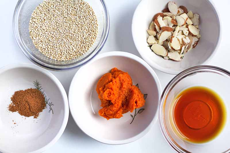 Horizontal overhead image of three white ceramic and two clear glass bowls of quinoa, sliced almonds, warming spices, roasted orange squash puree, and maple syrup, on a white surface.