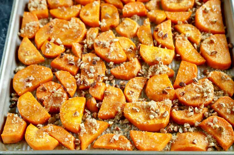 Horizontal oblique overhead image of roasted half-moon sliced and peeled orange sweet potatoes in a baking pan, topped with chopped pecans.