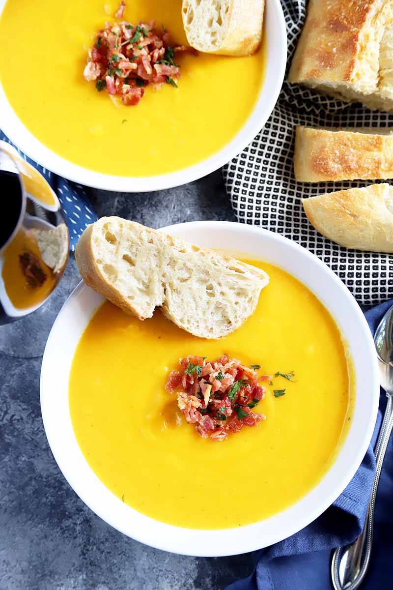 Vertical top-down image of two white bowls with orange soup, bread slices, and bacon.
