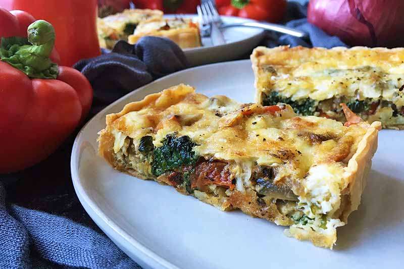 Horizontal close-up image of slices of vegetable quiche.