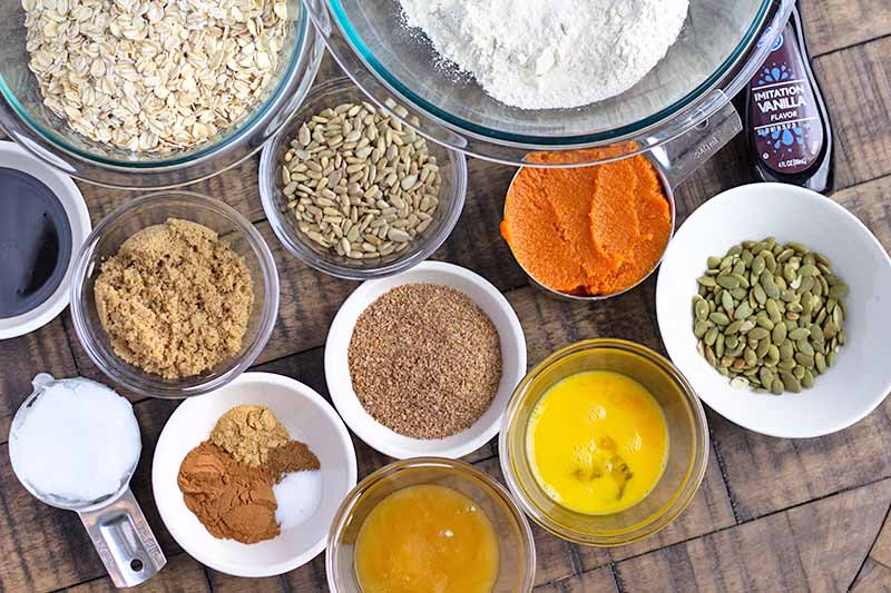 Horizontal image of assorted ingredients in various bowls to make a granola recipe.