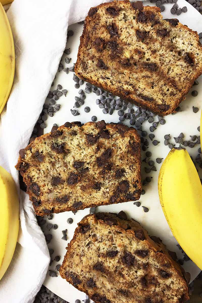 Vertical top-down image of three slices of chocolate chip banana bread.