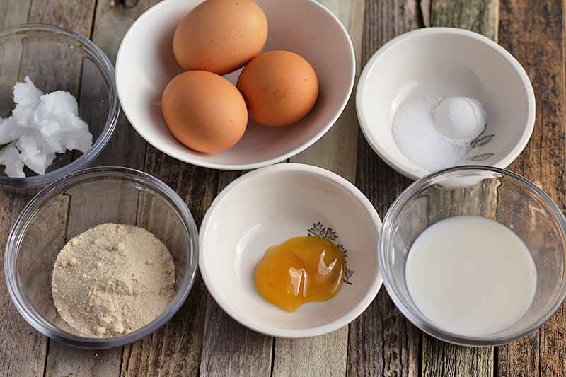 Horizontal image of assorted wet and dry ingredients in bowls, as well as a bowl of three eggs, on a light wooden surface.