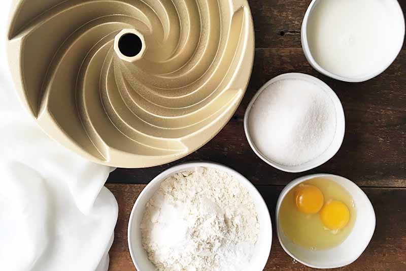 Horizontal image of assorted white ingredients in white bowls and eggs in a white bowl and a bundt pan on the side.