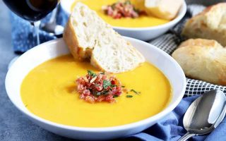 Horizontal image of a white bowl with orange soup, and slices of bread and bacon crumbles.