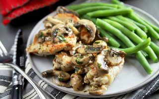 Horizontal image of a white plate with seared thighs and sliced mushrooms and green beans next to a striped napkin, a fork, and knife.