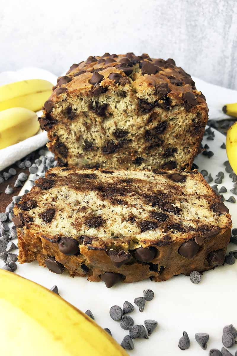 Vertical image of a thick slice of quick bread next to the whole loaf surrounded by fruit and candies.