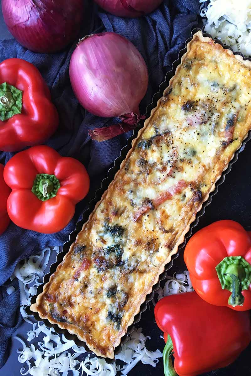 Vertical image of a whole rectangular savory tart next to red peppers and red onions on a dark surface.